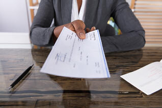 Black Person Handing Check Across Desk