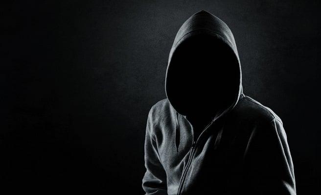 Black hooded figure against black background.