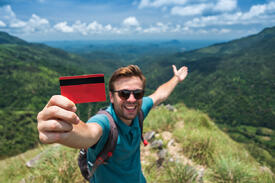 Man holds a credit card and points towards green hills