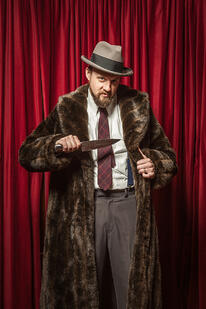 Man in Fur Coat and Fedora Holds Knife in front of Red Curtain