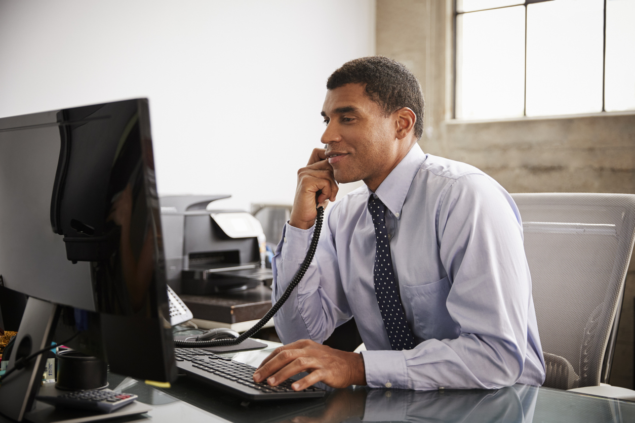 Professional Black Man at Office Desk on the Phone