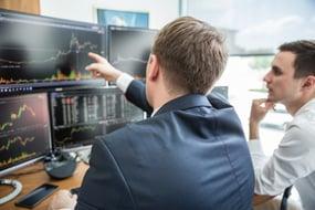 businessmen looking at screens