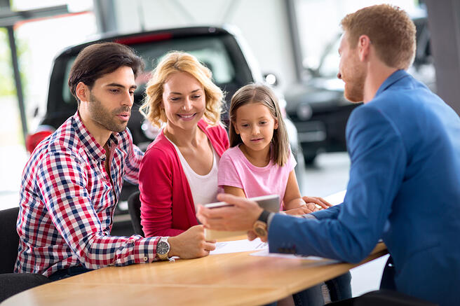 family buying car at auto dealership