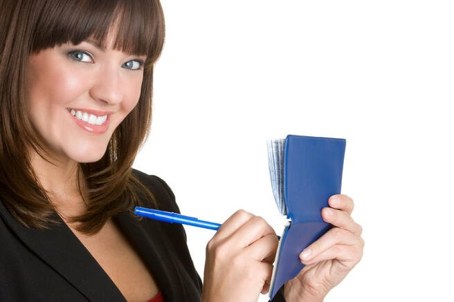 Woman smiling writing a check