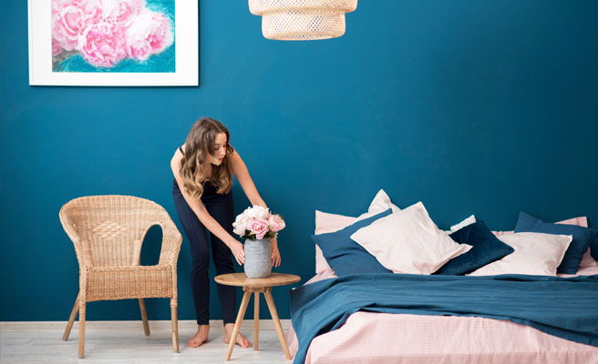 Woman placing flowers furnished room