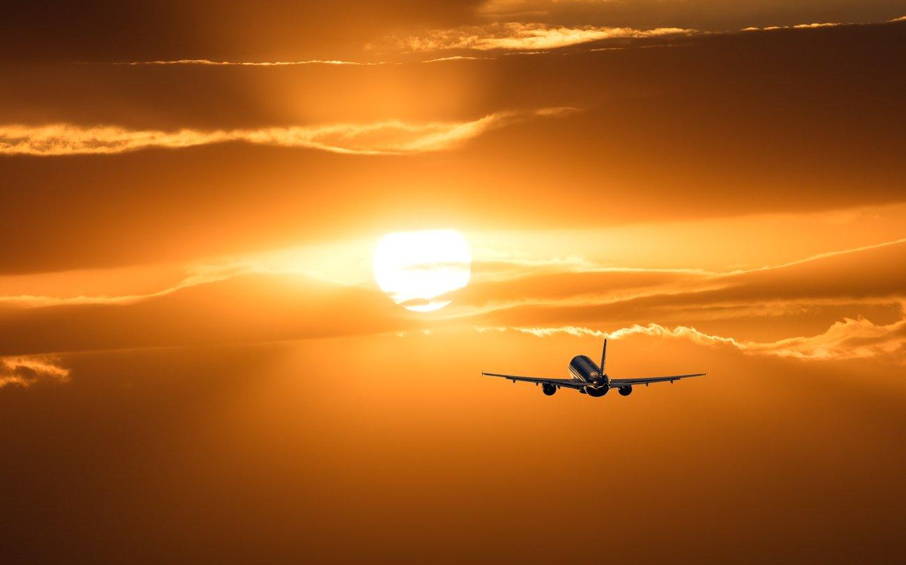 jet flying at sunset