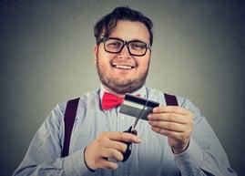 man cutting credit card