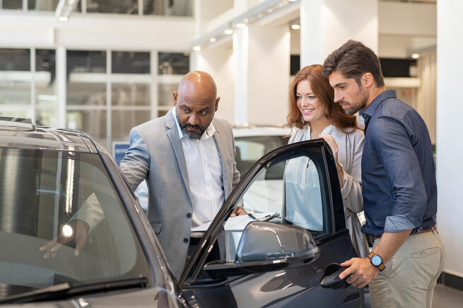 salesman showing car to couple